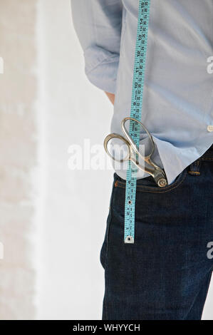 Midsection of young tailor with scissors in pocket and measuring tape standing in fashion studio - Stock Photo