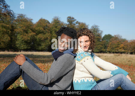 Side view of young multiethnic couple sitting back to back in park - Stock Photo