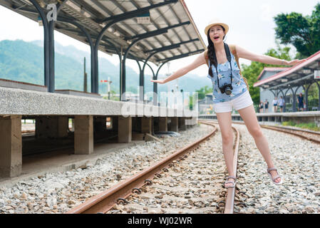 Beauty young woman walking on railway track balancing with her arms extended. The railroad is in a train station. The woman has a casual look and havi - Stock Photo