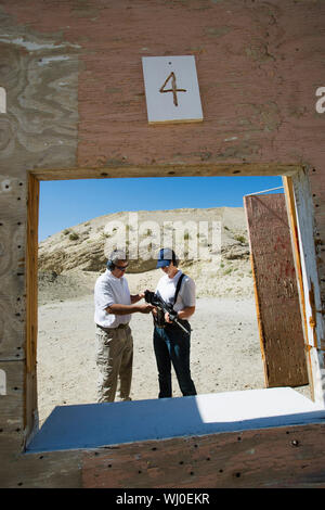 Instructor assisting woman loading gun at firing range in desert - Stock Photo