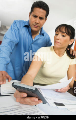 Middle woman showing calculation to man at home - Stock Photo