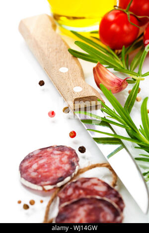 Close-up traditional sliced meat sausage salami with knife and vegetables - Stock Photo