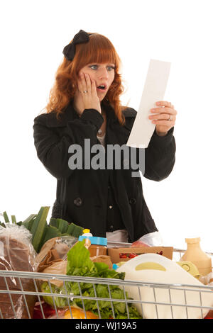 Woman with shopping cart full with dairy grocery products isolated over white background - Stock Photo