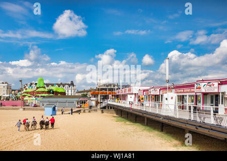 20 June 2019: Great Yarmouth, Norfolk, UK - Children riding donkeys on the beach, rear view, beside the pier. - Stock Photo