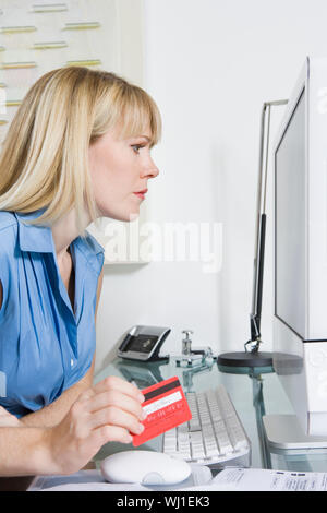 Pretty businesswoman looking intently on computer screen while holding credit card - Stock Photo