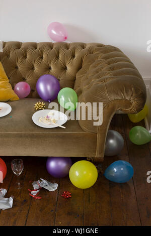 View of colorful balloons scattered around sofa in house - Stock Photo