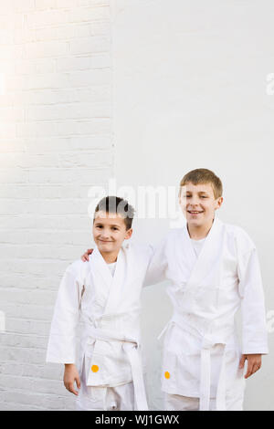Portrait of two smiling young boys dressed in karate costume - Stock Photo