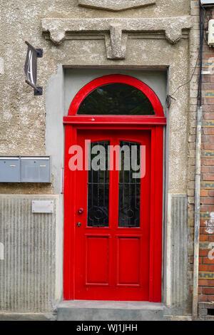 red door in a dilapidated building deterioration, Bucharest Romania - Stock Photo