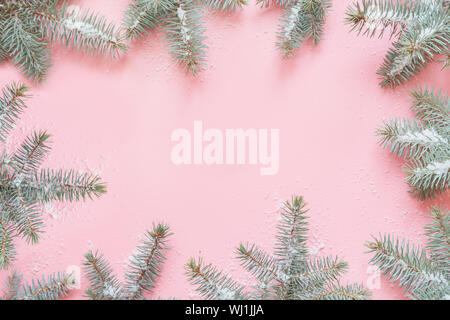 Christmas frame made of fir branches on pink table. Xmas background. Flat lay. Top view with copy space - Stock Photo