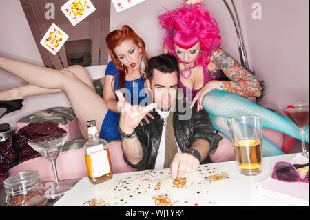 Man tossing playing cards in air with women sitting besides him - Stock Photo