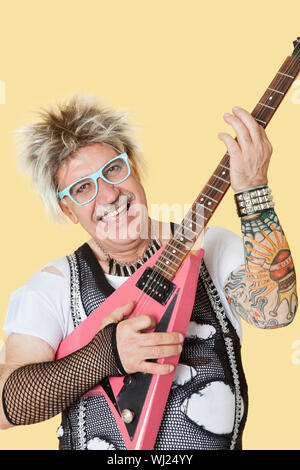 Portrait of happy senior male punk rock musician playing guitar over yellow background - Stock Photo