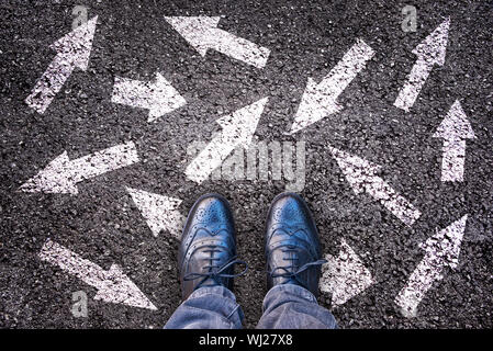 Sneaker shoes and arrows pointing in different directions on asphalt ground, choice concept - Stock Photo