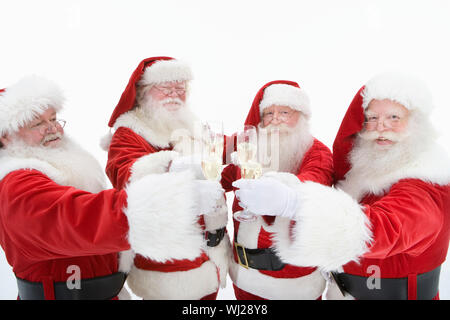Four Caucasian Santa Claus toasting champagne isolated over white background - Stock Photo