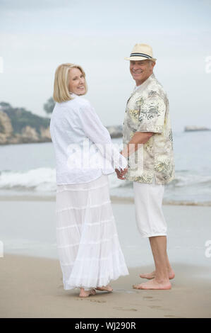 Full length portrait of a happy senior couple holding hands while standing at beach - Stock Photo