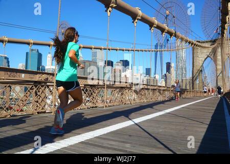 Woman jogging on Brooklyn Bridge, New York - Stock Photo