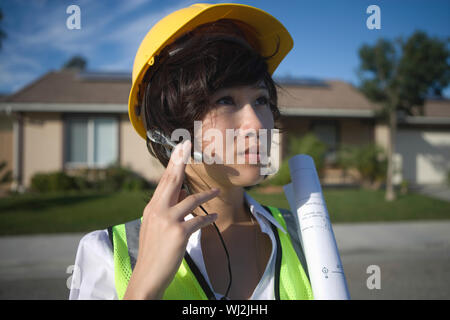 Young female solar panel worker with blue print wearing headset outdoors - Stock Photo