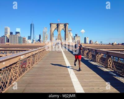 Man running over Brooklyn bridge in New York - Stock Photo