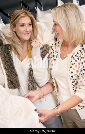 Happy mother and daughter looking at each other while selecting wedding dress in bridal boutique - Stock Photo