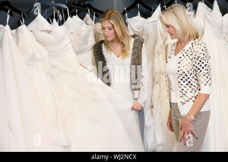 Young woman with senior mother selecting wedding dress in bridal store - Stock Photo