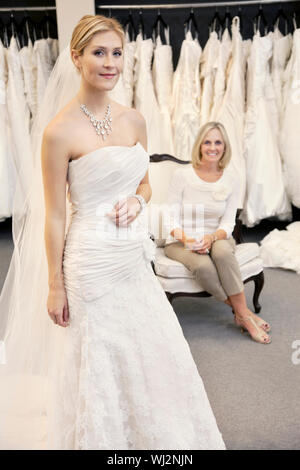 Portrait of a beautiful young woman in wedding dress with mother sitting background - Stock Photo