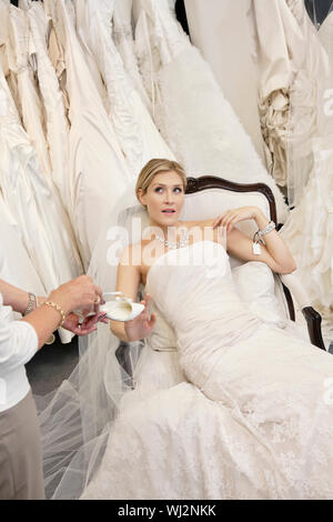 Tired young bride in wedding dress sitting while mother showing footwear - Stock Photo