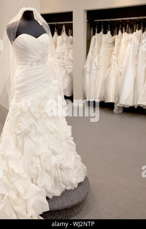 Elegant wedding dress displayed on mannequin in bridal store - Stock Photo