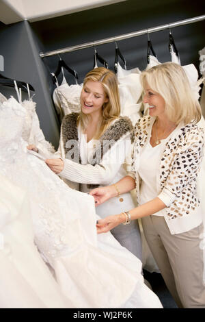 Cheerful young daughter with senior mother selecting wedding dress in bridal boutique - Stock Photo