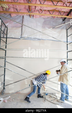 Male and female worker standing under scaffold at construction site - Stock Photo