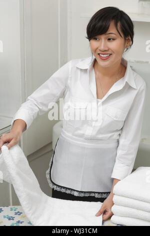 Female housekeeper looking away while folding white towel - Stock Photo