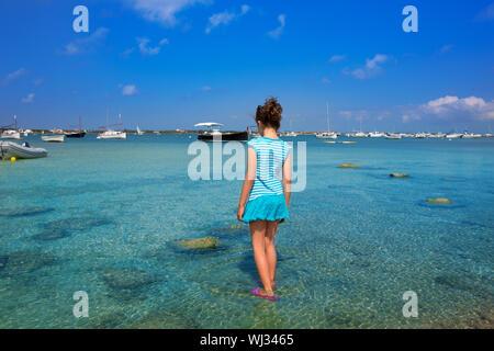 Kid girl walking at formetera in Estany des Peix lake rear view - Stock Photo