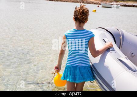 Kid girl in inflatable boat at formentera Estany des Peix near Ibiza - Stock Photo