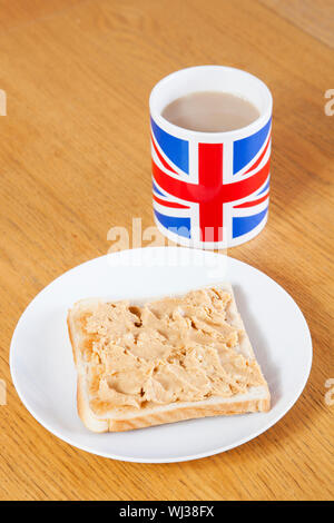 British coffee mug and slice of bread with butter on table - Stock Photo