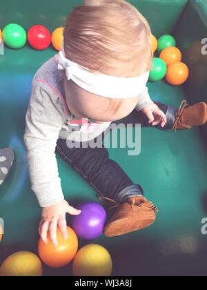 High Angle View Of Baby Boy Playing With Colorful Balls In Ball Pool - Stock Photo
