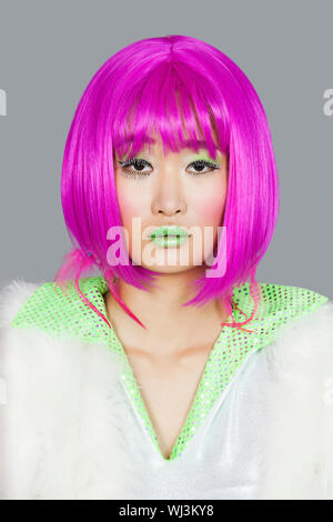 Portrait of young woman wearing pink wig over gray background - Stock Photo