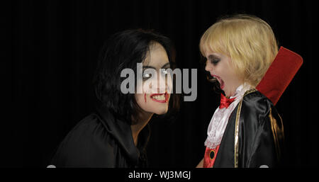 Woman and child dracula making faces. Little girl with her mother. Halloween make-up. Vampire kid with blood on her face. Happy Halloween holiday horror concept. Friday 13th theme - Stock Photo