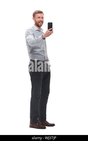 in full growth. smiling young businessman taking selfie - Stock Photo