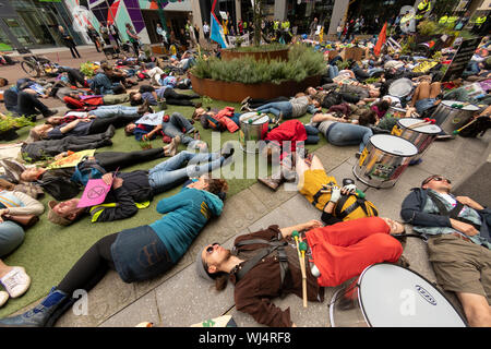 After showing support for 3 anti0fracking protesters attending Manchester Cuivil Justice Centre, they marched through the city streets and held a 'Die In' protest outside Barclays Building and Manchester City Council office in the Arndale centre. The march continued through the narrow streets of the Northern Quarter. - Stock Photo