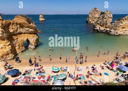 Tourists sunbathing and swimming on sunny, summer beach, Lagos, Algarve, Portugal - Stock Photo