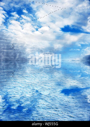 Geese in migration flight formation with beautiful dramatic cloud filled blue sky reflected over water - Stock Photo