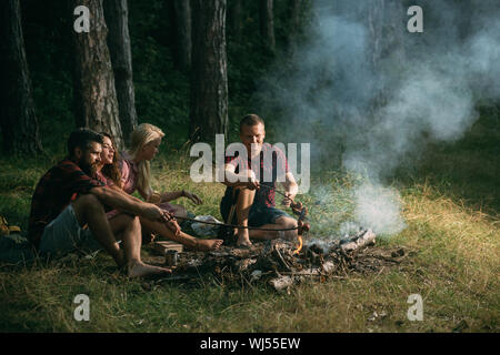 Two couples camping in woods. Cooking sausages on campfire. Warm summer evening in forest - Stock Photo