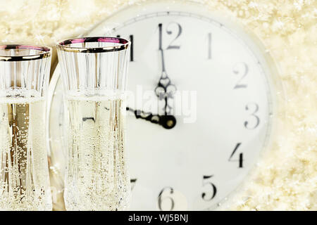Glasses and clock at midnight on New Year's Eve. - Stock Photo