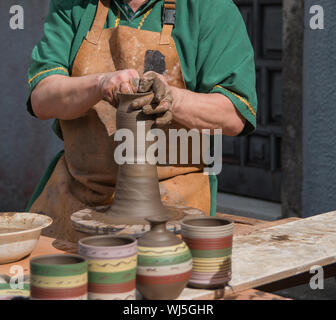 Potter working the mud with his hands - Stock Photo