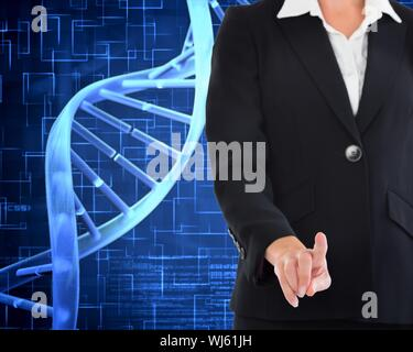 Composite image of businesswoman pointing at waist level next to dna spiral on blue background - Stock Photo