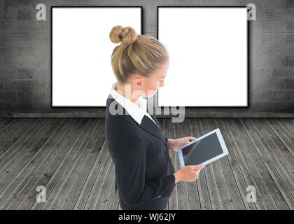 Composite image of blonde businesswoman holding tablet in 3d room in front of two scrrens - Stock Photo