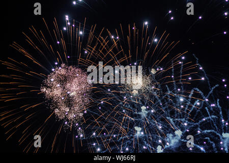 Salute, fireworks in the night sky. Pyrotechnic show on a holiday. Explosion of many firecrackers. - Stock Photo
