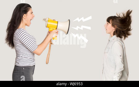 Angry mother shouting through megaphone at girl - Stock Photo