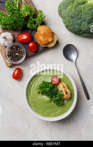 Ingredients for broccoli cream soup on beige background with cream soup in white bowl. Broccoli, parsley, garlic, salt, pepper, cherry tomatoes, roast - Stock Photo