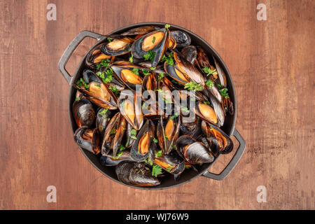 Marinara mussels, moules mariniere, cooked in a cooking pan, shot from above on a dark rustic background - Stock Photo