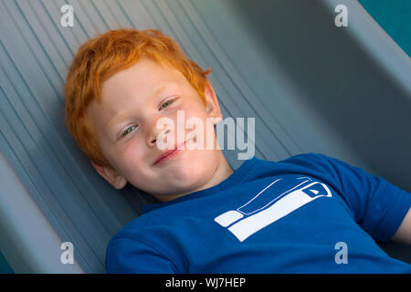 Boy lying on the floor. Portrait European boy with green eyes, looking directly at the camera. Overhead view. Funny little child with curly ginger