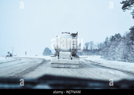 Truck with cargo tank on slippery snow winter road outside the city, back view - Stock Photo